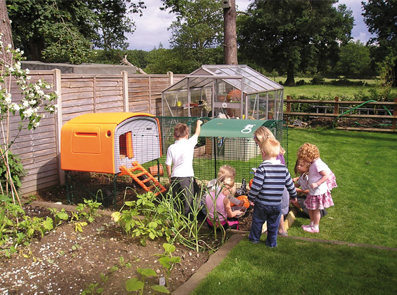 Children around the Eglu Cube chicken house.